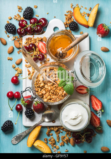 Healthy breakfast ingredients. Oat granola in open glass jar, yogurt, fruit, berries, honey and mint on blue background - Stock Image