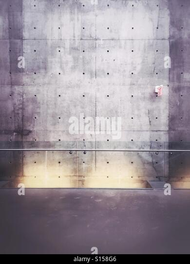 An exit sign hangs on a bare concrete wall behind a glass railing. - Stock Image