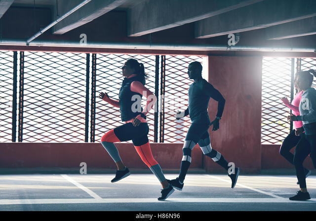 Side view of young athletes exercising in front of big windows. Copyspace - Stock-Bilder