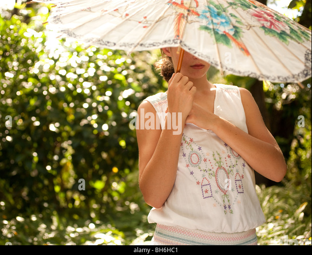 A young girls stands in her garden and daydreams under her Chinese umbrella. - Stock Image