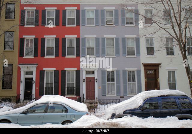 Washington DC Capitol Hill neighborhood townhouses building parked car covered in snow winter weather - Stock Image