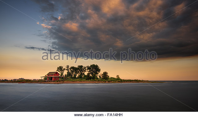 Guilford Grass Island with its iconic red little hut during sunset with a massive cloud looming over it - Stock Image