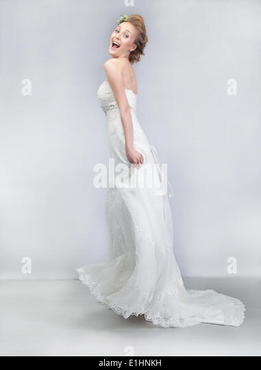 Wedding dance - joyful young funny fiancee in long bridal white dress studio shot - Stock Image