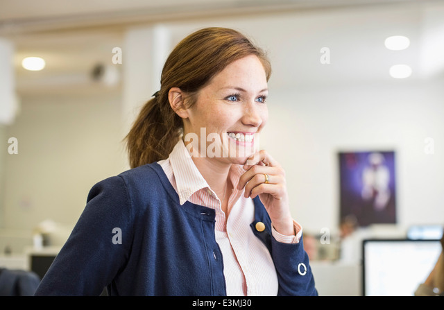 Smiling businesswoman with hand on chin looking away in office - Stock Image