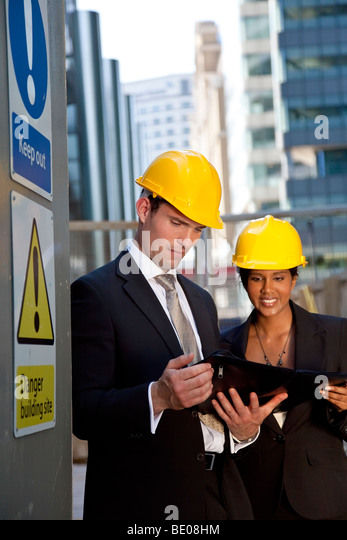 A male manager on a construction site wearing a hard hat and talking with his Asian female colleague - Stock Image
