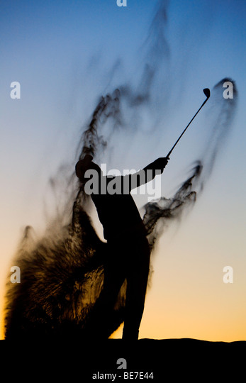 Silhouette of a golfer late in the day - Stock Image