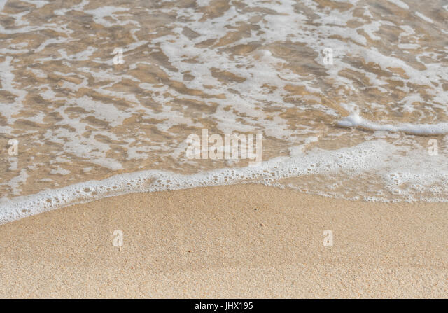 Close Up of Ocean Ripples on Beach  with sandy coast - Stock Image