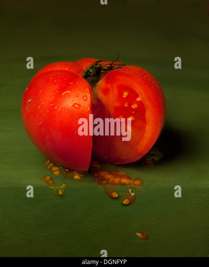 Sliced tomato on green backdrop - Stock Image