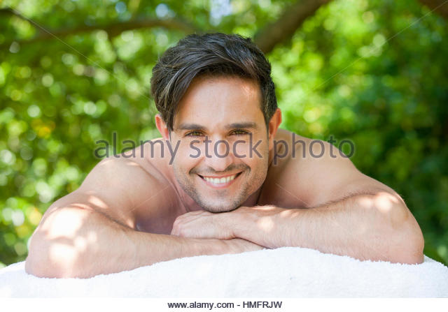 Portrait happy brunette man laying on massage table under tree - Stock-Bilder