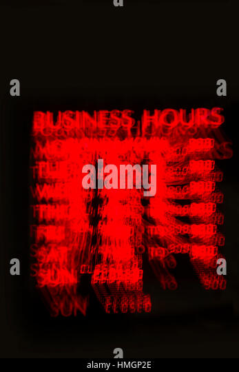 A business hours sign with a partial zoom effect. - Stock Image