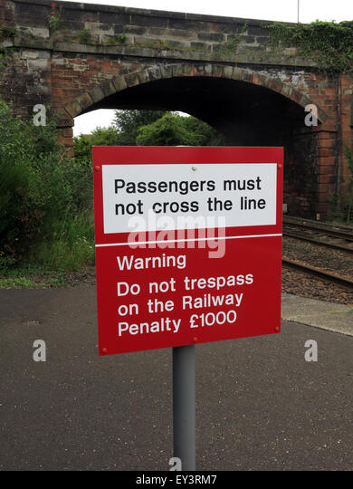 Passengers must not cross the line sign on railway platform - Stock Image