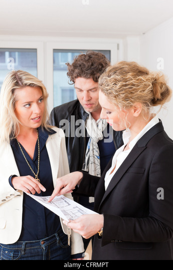Young realtor explain lease agreement or purchase contract with floor layout to couple in an apartment, close-up - Stock Image