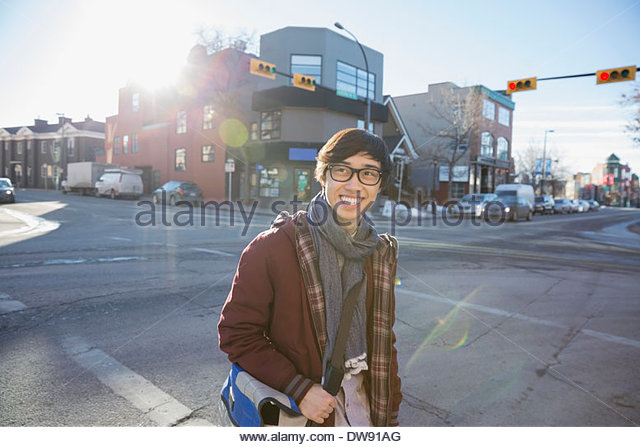 Young man standing on city street - Stock Image