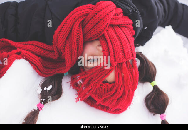 Girl with red scarf covering face lying in the snow - Stock Image