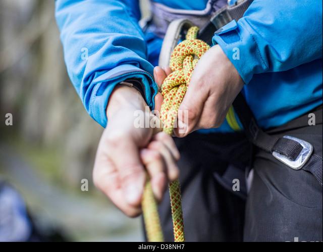 Rock climber tying rope - Stock Image