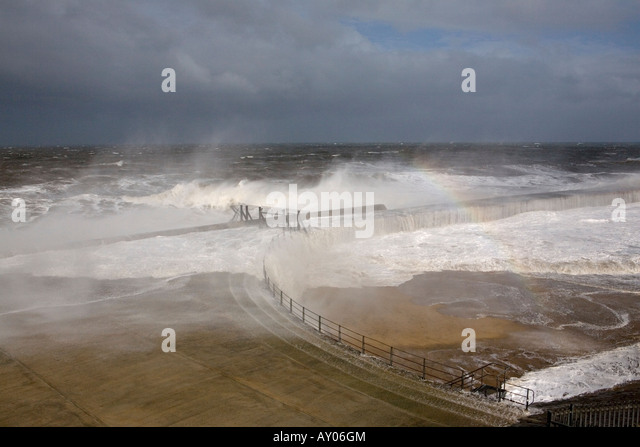 A violent and severe gale blows waves through the locked gates of Seaham Pier in County Durham creating a rainbow - Stock Image
