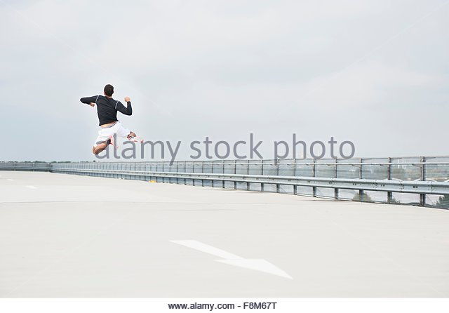 Rear view of young male runner jumping for joy on parking lot roof - Stock Image