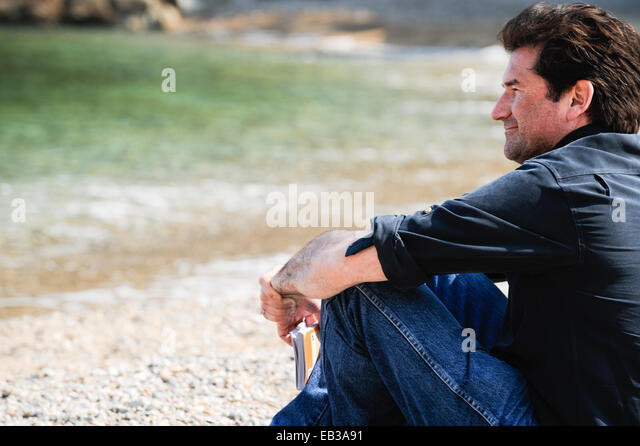Man sitting on beach holding a guide book, Sa Tuna Beach, Begur, Girona, Catalonia, Spain - Stock Image