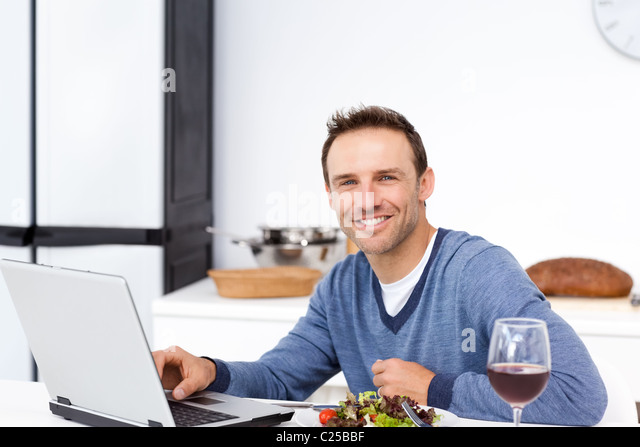 Happy man looking at his laptop while eating a salad - Stock-Bilder