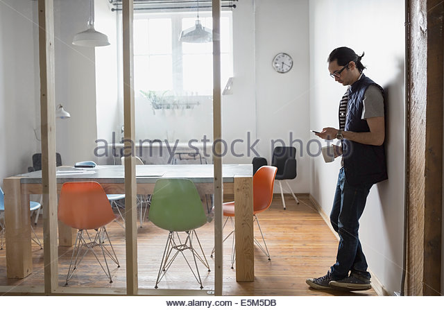 Businessman using cell phone in conference room - Stock-Bilder