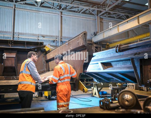 Engineers discussing engineering drawings in factory - Stock-Bilder
