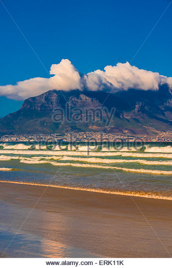 View of Cape Town and Table Mountain and Lion's Head Peak from the beach at Milnerton, South Africa. - Stock Image