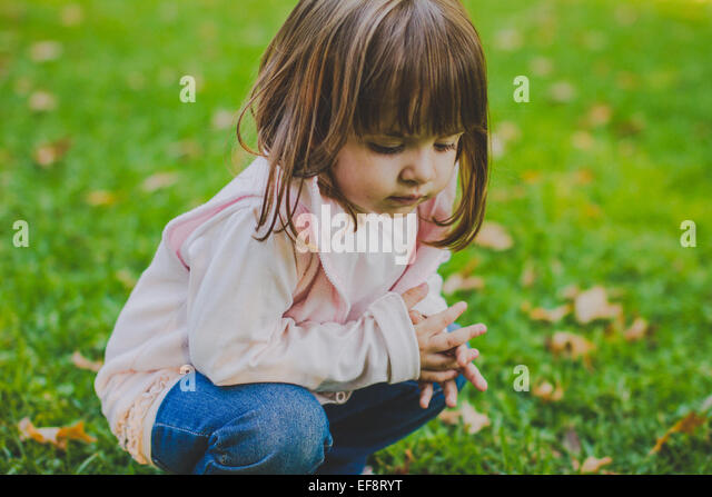 Portrait of girl (2-3) crouching on grass - Stock Image