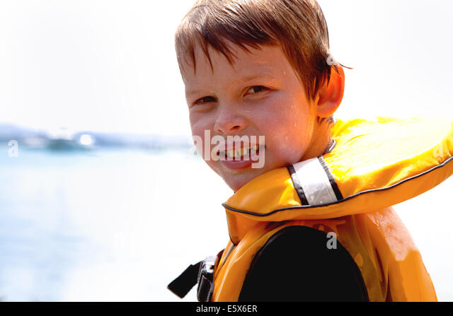 Close up portrait of smiling boy in lifejacket - Stock Image