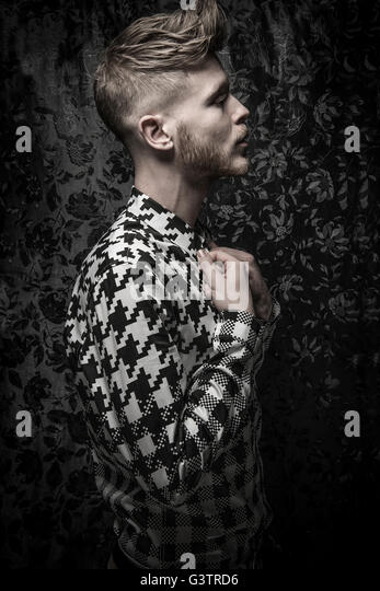 Studio portrait of a bearded young man in a black and white shirt. - Stock Image