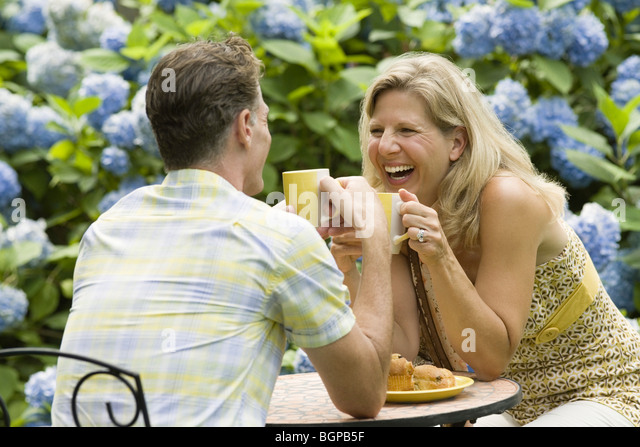 Mature couple having tea in a lawn and laughing - Stock Image