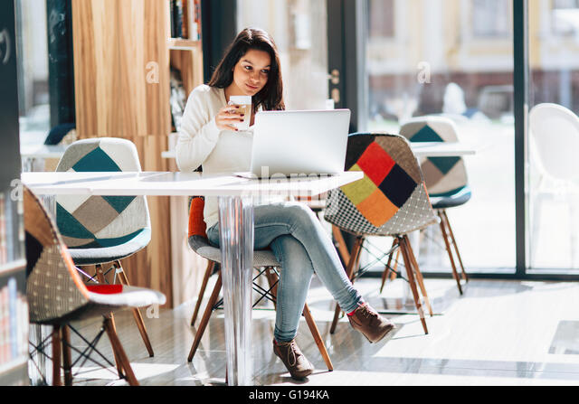 Beautiful brunette enjoying coffee and using laptop - Stock Image