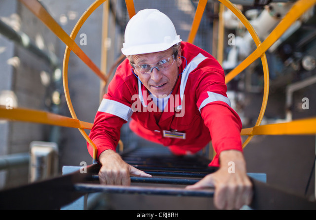 Worker climbing ladder at oil refinery - Stock Image