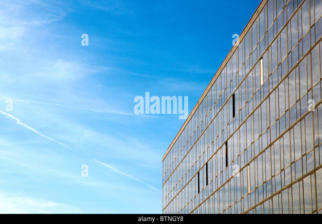Modern building under blue sky with clouds - Stock Image