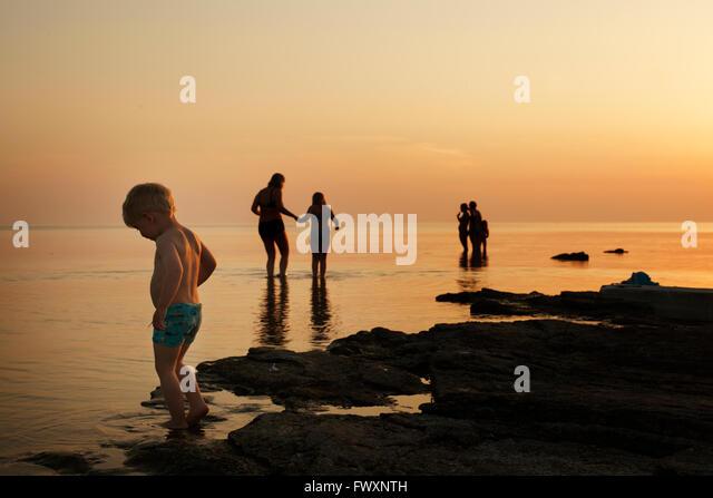 Sweden, Gotland, Faro, Boy (2-3) with family on beach at dusk - Stock-Bilder