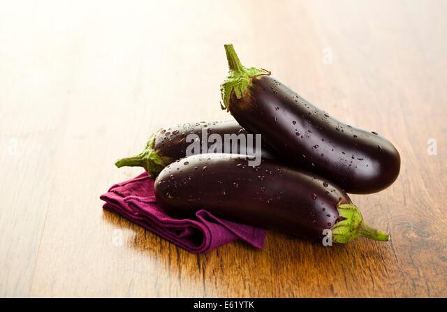 Raw aubergines or eggplants on wooden backround. - Stock Image