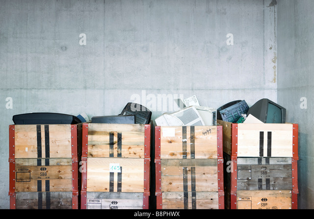 Discarded electronics in crates stacked in recycling center - Stock Image
