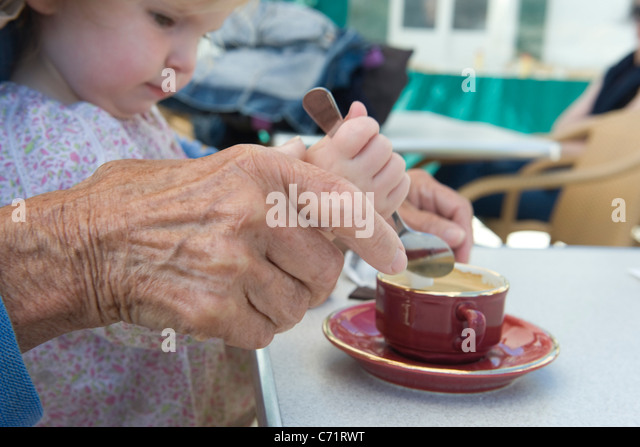 Toddler girl helping grandmother stir cup of coffee, cropped - Stock Image