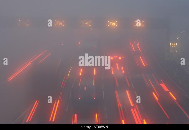 Lights streak Northwards during dawn fog makes car driving hazardous on M25 motorway at crossing of Dartford Bridge - Stock Image