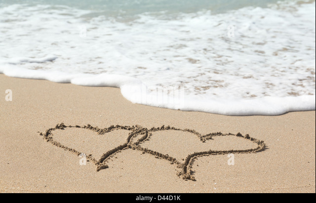 Linked love hearts drawn in the sand on a tropical beach by ocean surf - love holiday vacation romance concept - Stock-Bilder