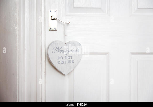 A funny Newlyweds 'Do Not Disturb' sign placed on the bedroom door of the honey moon suite for the newly - Stock Image