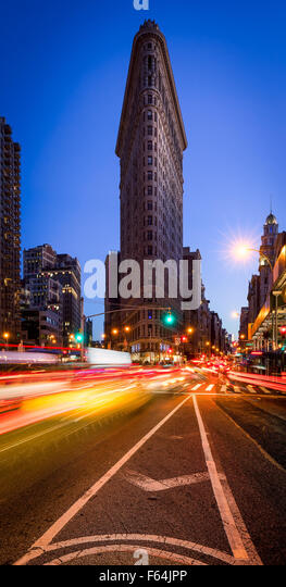 Flatiron Building with a clear blue sky and car light trails on 5th Avenue at dusk in Midtown Manhattan, New York - Stock Image
