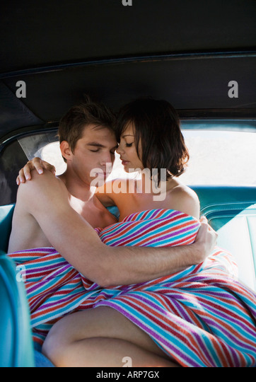 Man and woman on backseat of car - Stock Image