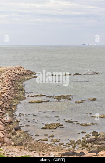 Ship at La Plata river in Montevideo with stones and cloudy sky. - Stock Image