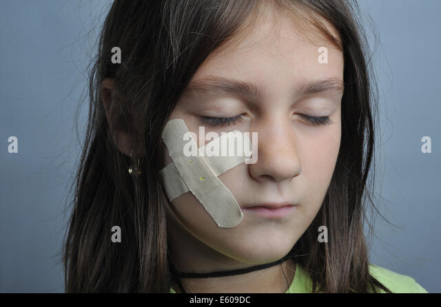 Little girl, close up portrait, with adhesive bandage on face - Stock Image