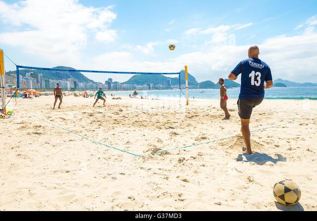 RIO DE JANEIRO - MARCH 15, 2016: Brazilian men play futevôlei (footvolley, combining football and volleyball) - Stock Image