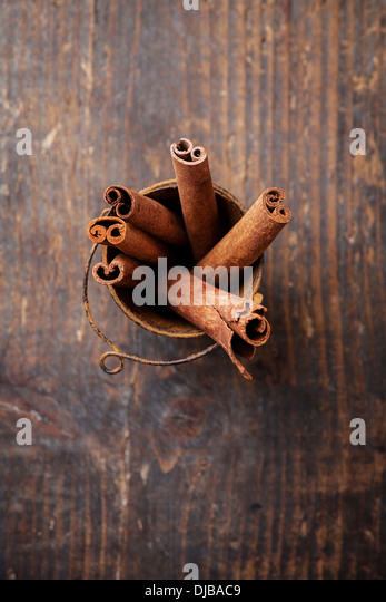 Cinnamon sticks in bucket on wooden background - Stock Image