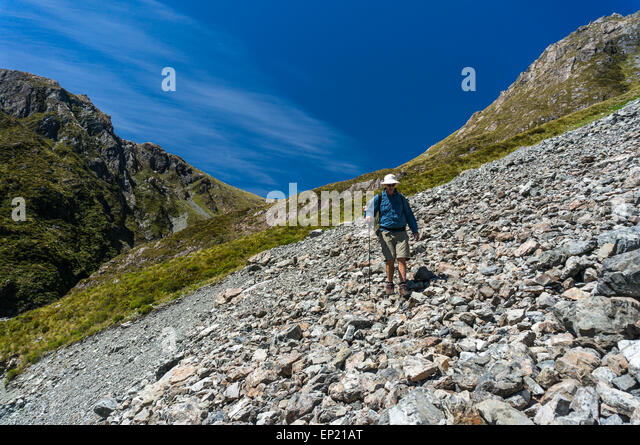 Man walking Across a Scree Slope in Arthur's Pass National Park, New Zealand - Stock Image