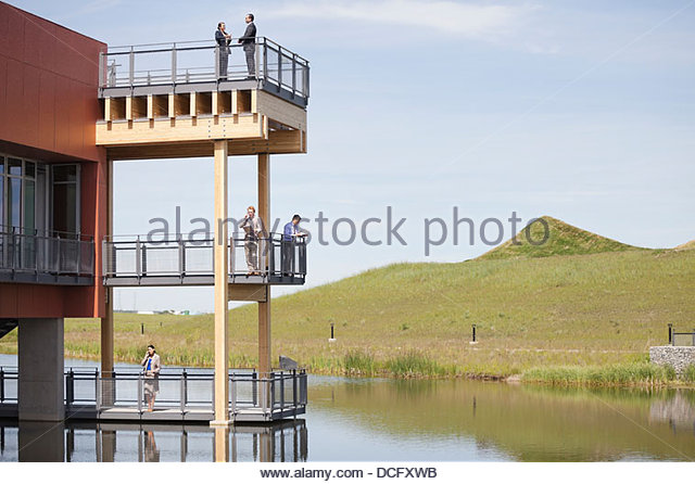 Business people standing on multiple office balconies - Stock Image