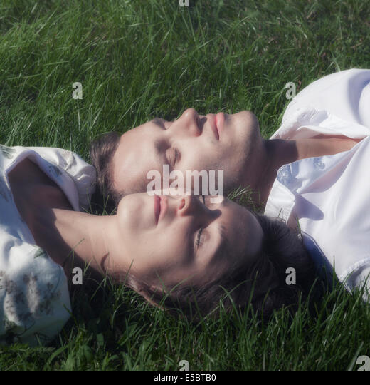 a couple sleeping in the grass - Stock-Bilder
