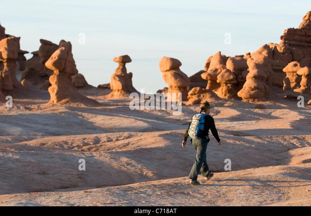 Woman hiking through hoodoos in Goblin Valley State Park, Hanksville, Utah. - Stock Image